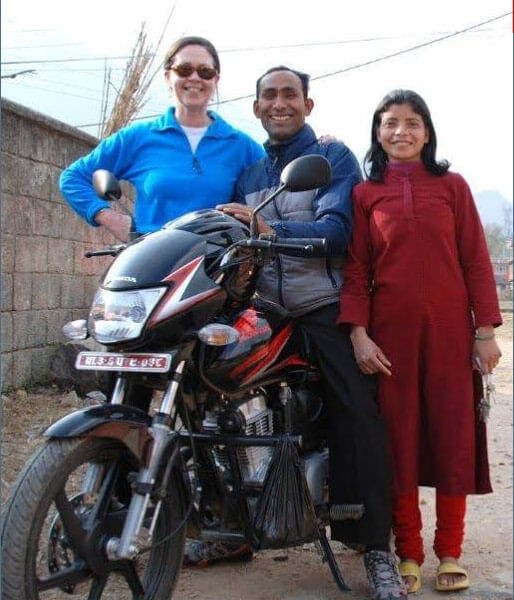 Dipak sitting on his scooter with Maggie and Sumitra standing next to him